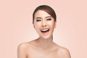 Beauty portrait of skin care beauty woman laughing smiling happy and cheerful. Asian female beauty model on pink background.