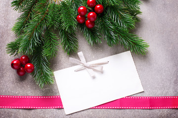 Spruce branches, decorative berries and tag on grey slate  background. Christmas background. Selective focus. Place for text.