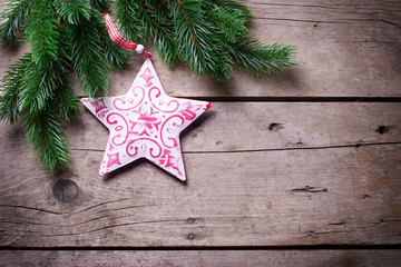 Spruce and decorative star  on wooden background.