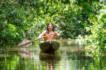 amazon tribe brazil indian ecuador indigenous native village people culture forest indigens mature male on symbolic wooden boat chopped from a single timber cruising murky waters of ecuadorian amazon
