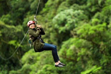 Afro Woman On Zip Line Against Blurred Forest