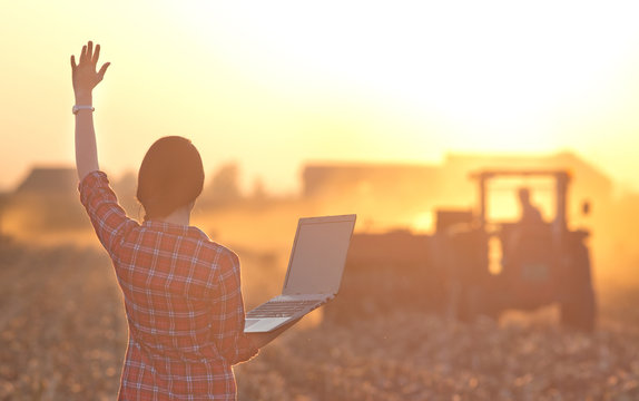 Woman with laptop and tractor