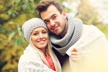 Fototapete - Young romantic couple in the park in autumn