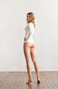 Beautiful and fit woman in white panties posing near the wall.