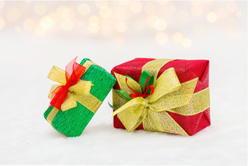 Red and green Christmas gift box with shiny golden ribbon. Bokeh with glow effect on white background