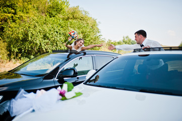 wedding couple at car sunroof