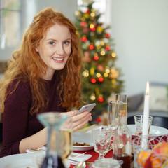 lächelnde frau sitzt am tisch während der weihnachtsfeier
