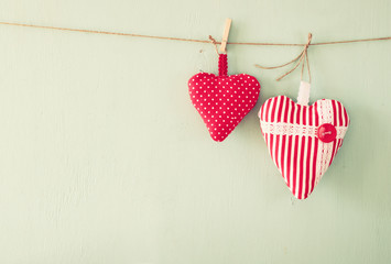 image of fabric hearts hanging on rope in front of wooden background. retro filtered