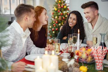 zwei paare feiern weihnachten zusammen bei einem gemütlichen essen