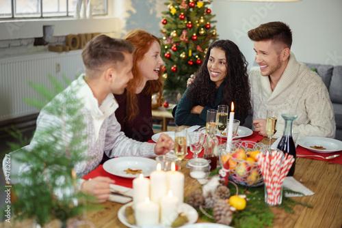 lachende freunde essen zusammen an weihnachten. Black Bedroom Furniture Sets. Home Design Ideas