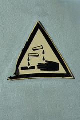 vergilbter Aufkleber mit dem Symbol Ätzend