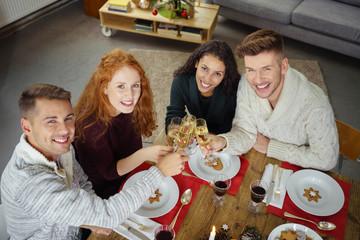 freunde stoßen mit sekt an beim gemütlichen weihnachtsessen zu hause