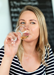 Woman drinking glass of white wine outdoors.