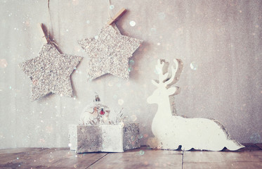 image of white wooden reindeer and glitter stars hanging on rope over glitter silver background