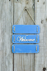 Blue welcome sign hanging on rustic fence