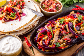 Pork fajitas with onions and colored pepper, served with tortill