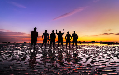 Group of men silhouette with sunset background