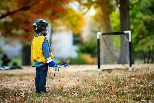 Little kid playing lacrosse with his stick in the autumn park