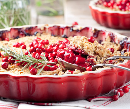 Cranberry, bilberry crumble with rosemary on a wooden background