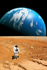 A stranded astronaut surveys his situation on a barren moon - Elements of this image furnished by NASA.