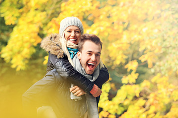 Fototapete - Young romantic couple piggybacking in the park in autumn
