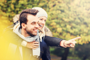 Fototapete - Young romantic couple pointing in the park in autumn