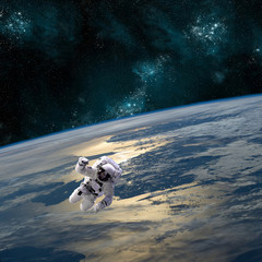 Fototapete - An astronaut floats above Earth - Elements of this image furnished by NASA.