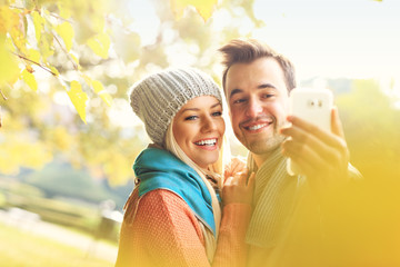 Fototapete - Young romantic couple taking selfie in the park in autumn