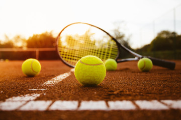 Tennis balls with racket on clay court