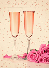 Composition with pink sparkle wine in glasses, and pink roses on beige with hearts background
