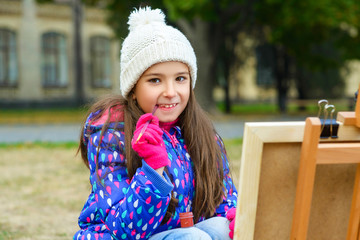little cute girl draws paints on an easel outdoors
