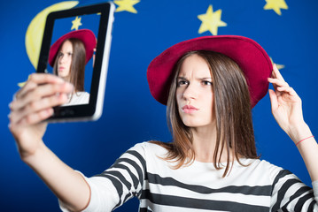 Beautiful young woman making selfie and frowning on blue screen
