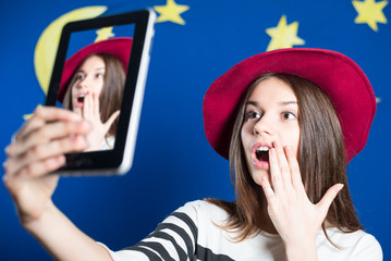 Picture of beautiful excited young lady in hat making selfie by tablet