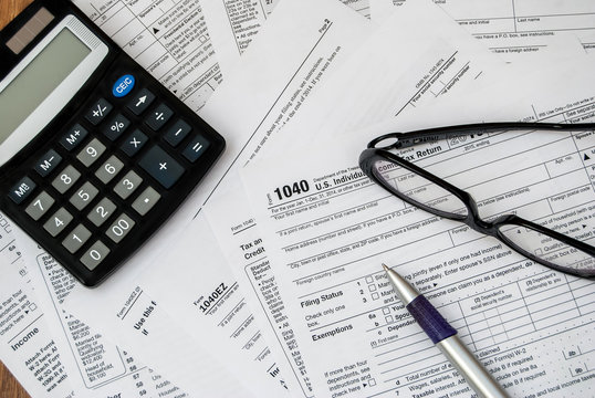 pen, glasses and calculator on the tax form