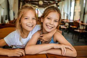 Little beautiful cheerful sisters in restaurant