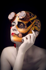 Bald girl with a art make up and steampunk glasses, on the one hand a mechanical robot, on the other blooming desert