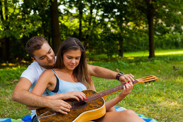 Young man teaches his girlfriend to play the guitar.