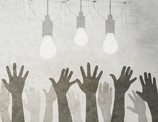Idea concept with light bulbs and  raised hands on grunge background.