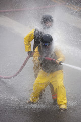 Men dressed in yellow firemen slickers and firehoses have annual Waterfight on July 4, Main Street, Ouray, CO, sponsored by Ouray Fire Department.