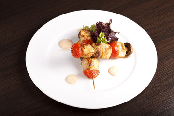 Chicken kebab on skewers with tomatoes