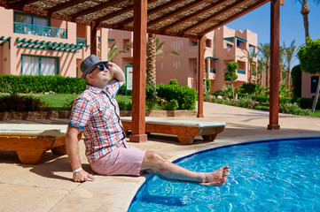 Happy man in a hat sitting on the edge of the pool