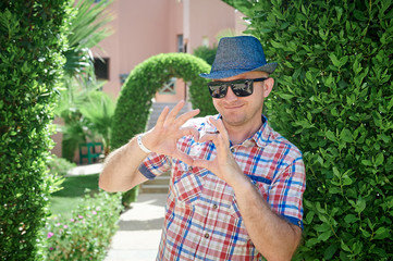 man in a hat and sunglasses makes the heart with fingers