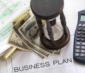 A business plan lying on a desk with hourglass, calculator and hundred dollar bills on a stack of newspapers.