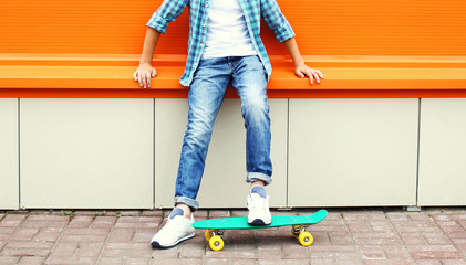 Stylish teenager boy wearing a checkered shirt and jeans on skat