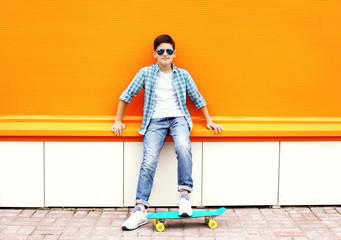 Stylish teenager boy wearing a checkered shirt, sunglasses on sk