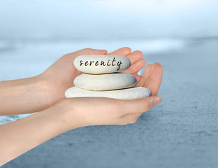 "Hands holding a small stack of pebbles with 'Serenity'""written on the top stone."