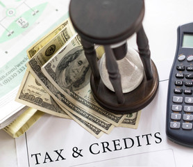 Tax and credits concept. Getting refund from the income tax return. Hourglass on financial documents