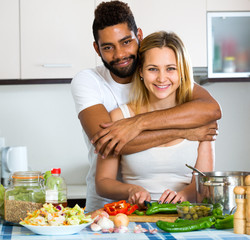 Husband helping wife preparing healthy dinner