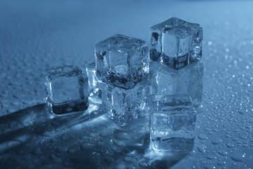 Melting ice cubes under blue light, close up