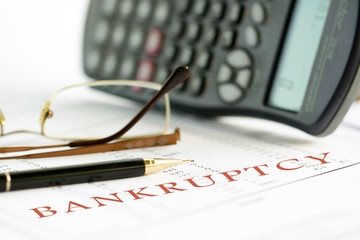 Bankruptcy concept image of a pen, calculator and reading glasses on financial documents